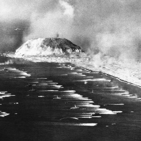 """""""I mezzi da sbarco dei Marines mentre stanno raggiungendo la spiaggia di Iwo Jima. Al centro -sulla sinistra- c'è il monte Suribachi, detto «Hot Rock» dai Marines che presero l'Isola. La foto -presa da un aereo- fu spedita a Guam, quindi trasmessa via radio e infine pubblicata su un quotidiano americano 15 ore dopo essere stata scattata"""""""