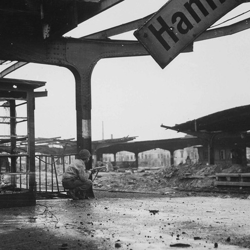 """""""Alert for enemy movement, Private First Class Armand Rindone, Philadelphia, Pennsylvania, crouches with a carbine at the railroad station in the newly captured town of Hamm, Germany."""" Additional Information About this Item   April 6, 1945 Hamm, Germany Author unknown or not provided © courtesy U.S. National Archives and Records Administration"""