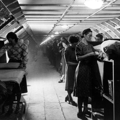 Rifugiati in un ricovero antiaereo preparano i loro letti a castello