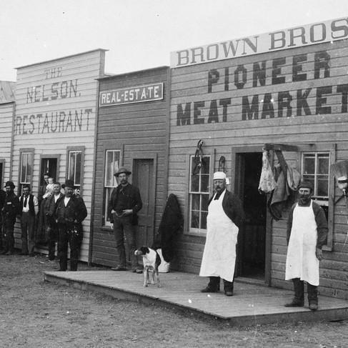 Negozianti e clienti in posa davanti agli edifici in legno in Broadway Street, nella città di Round Pond, oggi fantasma  Territorio dell'Oklahoma gennaio 1894 Foto di Robert Kennett Courtesy National Archives