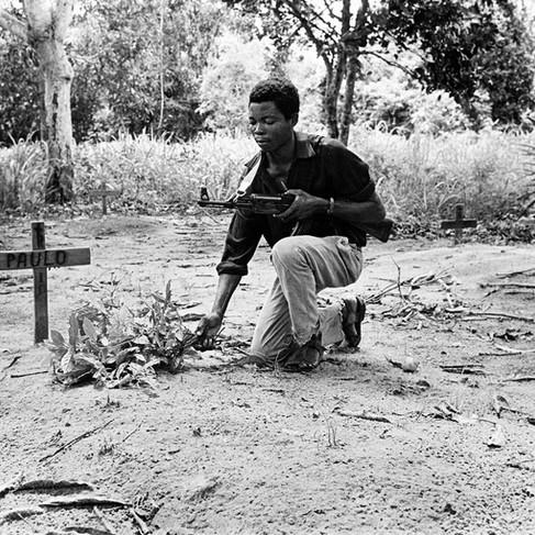 Un guerrigliero del Frelimo, il movimento di liberazione del Mozambico, sulla tomba di un compagno d'armi