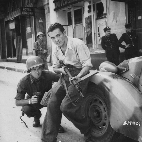 """""""American officer and French partisan crouch behind an auto during a street fight in a French city.""""  Summer, 1944 France Author Unknown or not provided © courtesy U.S. National Archives and Records Administration"""