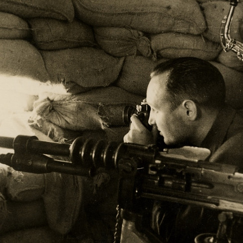 Due miliziani repubblicani (uno con in mano un sassofono e l'altro mentre scatta delle foto attraverso la feritoia) dentro a una postazione fortificata dei ribelli all'interno della caserma militare di Cuartel de la Montaña da cui i fascisti sparavano con mitragliatrici di grosso calibro