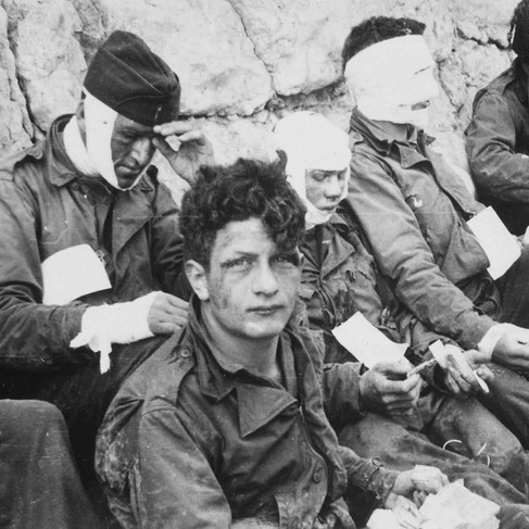 """""""American Assault Troops of the 16th Infantry Regiment, Injured While Storming Omaha Beach, Wait by the Chalk Cliffs for Evacuation to a Field Hospital for Further Medical Treatment""""   6 June 1944 Collville-sur-Mer, Normandy, France Author Unknown or not provided © courtesy U.S. National Archives and Records Administration"""
