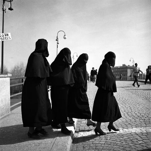 Donne turche attraversano la strada in una città macedone in Jugoslavia