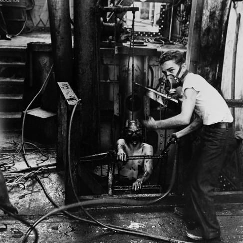 """""""Subacquei emergono da un compartimento pieno di gas a bordo di una delle navi che vengono soccorse dopo il raid giapponese del 7 dicembre 1941. Da notare l'olio diffuso sul ponte della nave e le maschere indossate dagli uomini"""""""