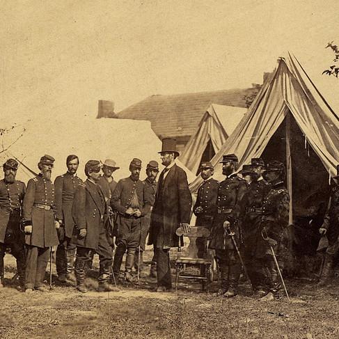 """Il Presidente Lincoln in visita al campo di battaglia di Antietam, per convincere """"Little Mac """", cioè il generale McClellan (comandante dell'Armata del Potomac), ad attaccare l'esercito confederato. Lincoln è in piedi appoggiato ad una sedia con di fronte McClellan e altri 15 ufficiali dell'esercito dell'Unione"""