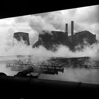 Nuvole di vapore salgono dalle torri di raffreddamento degli impianti per la produzione di acciaio alla Workington Iron and Steel Company. L'impianto, specializzato nella costruzione di rotaie, fu inaugurato nel 1856 e venne chiuso nel 1981