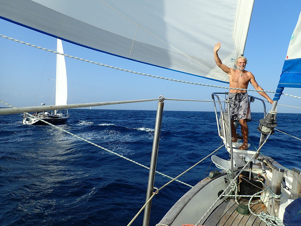 Angelo celebrating on the bow with another boat to port