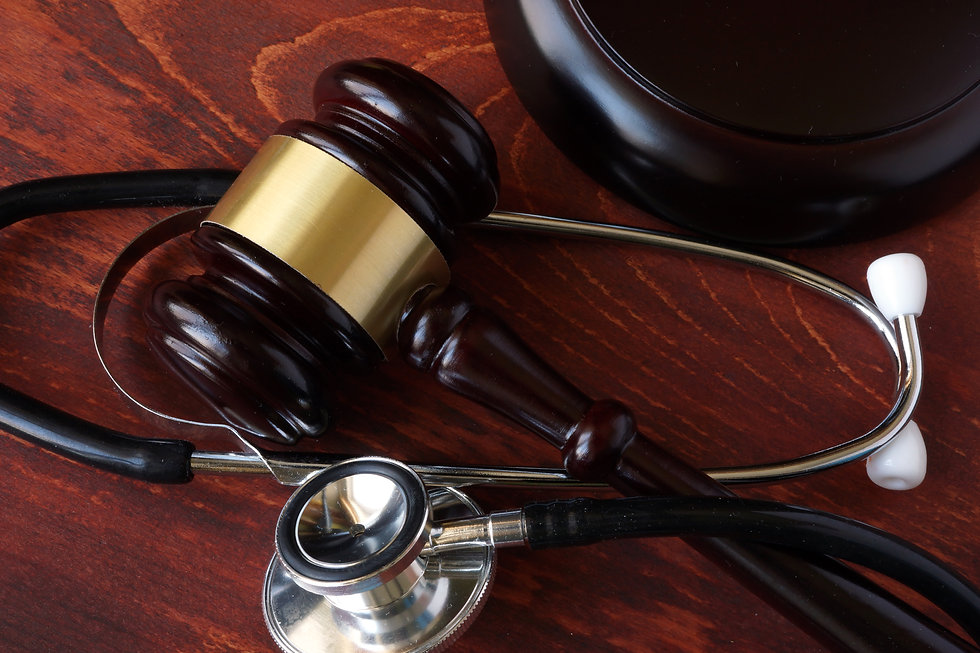 Gavel and stethoscope on a wooden surfac