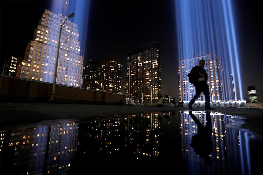 Pedestre passa diante do 'Tribulo em Luz', homenagem em Manhattan às vítimas dos atentados de 11 de Setembro, na noite de terça-feira (10), véspera dos 18 anos dos ataques — Foto: Andrew Kelly/Reuters
