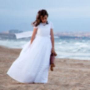 Niña vestida de comunión por la playa
