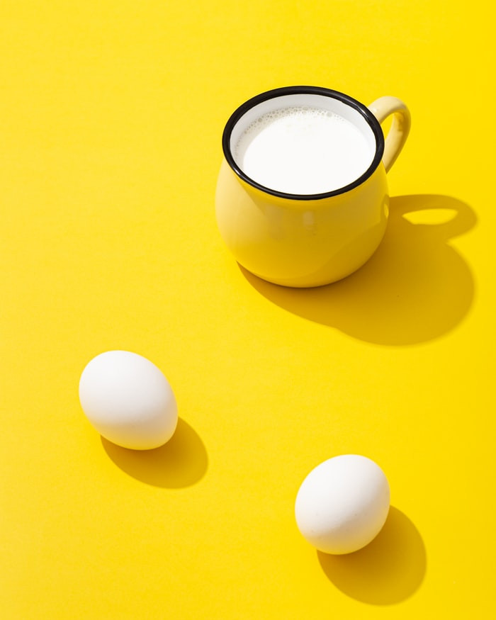 milk and eggs on a yellow background