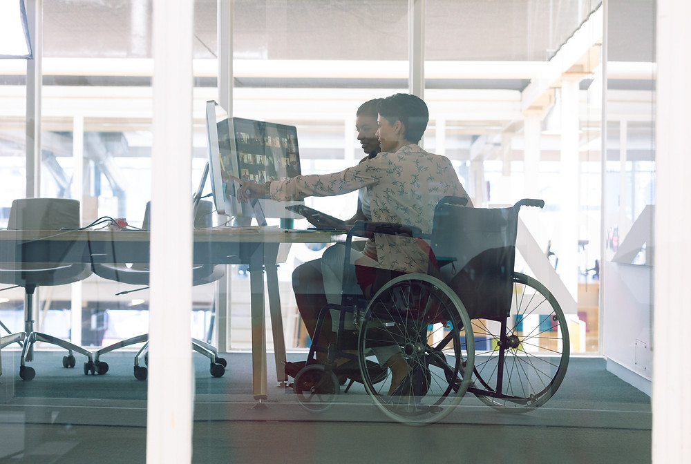 Image: Two people working at a desk in an office. One of them is a wheelchair user.