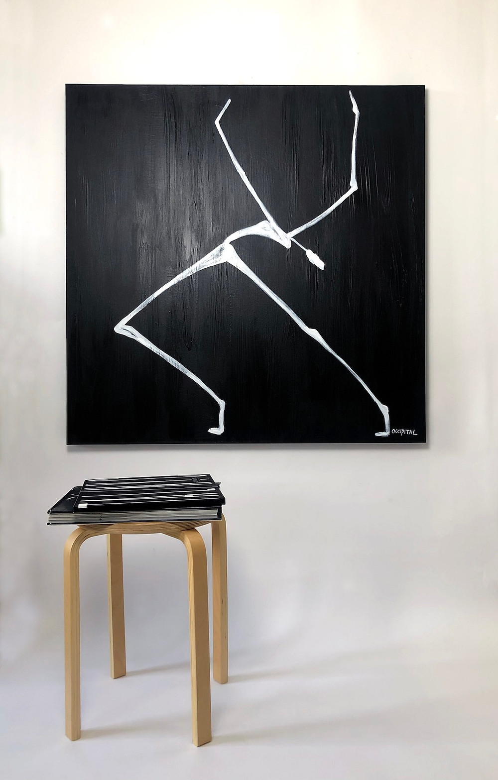 A painting is on a wall with a chair in front of it.  The painting is a black background and of figure painted with white paint.