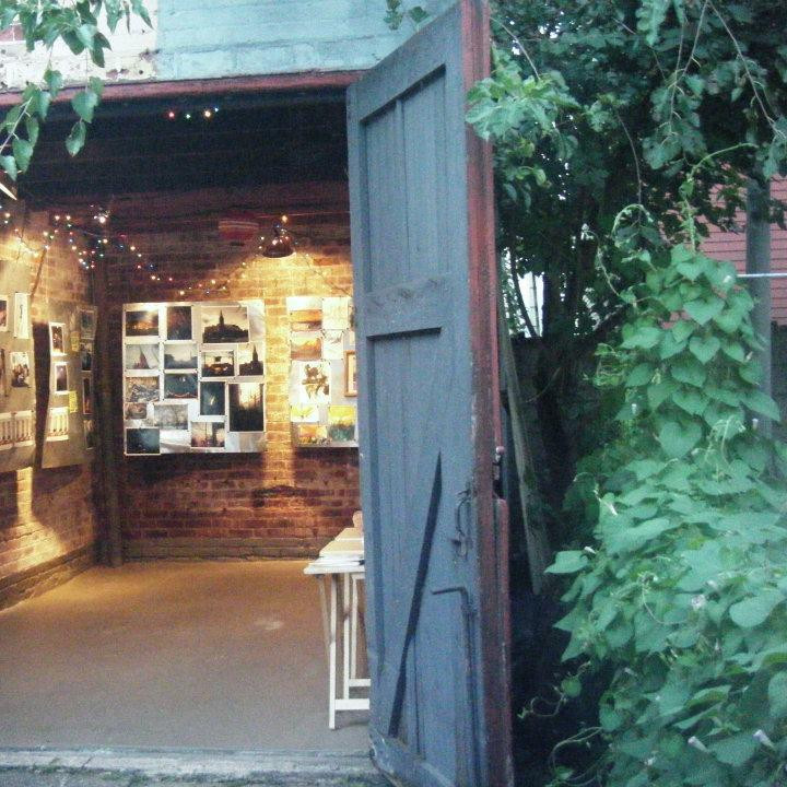 Entrance to Project Greenville converted shed backyard art space featuring a wooden door, brick walls and large pieces of suspended metal which art is displayed on using magnets.
