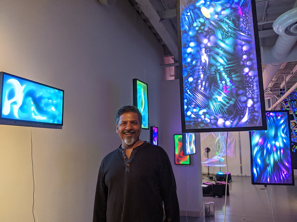 Artist Sunil Garg smiling in his exhibition, Boundless Light, which is lots of screens with projections of abstract bright colors,at NJCU Visual Arts Gallery