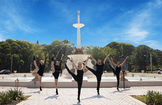 Five young dancers in black dance in front of the Lincoln Park fountain.