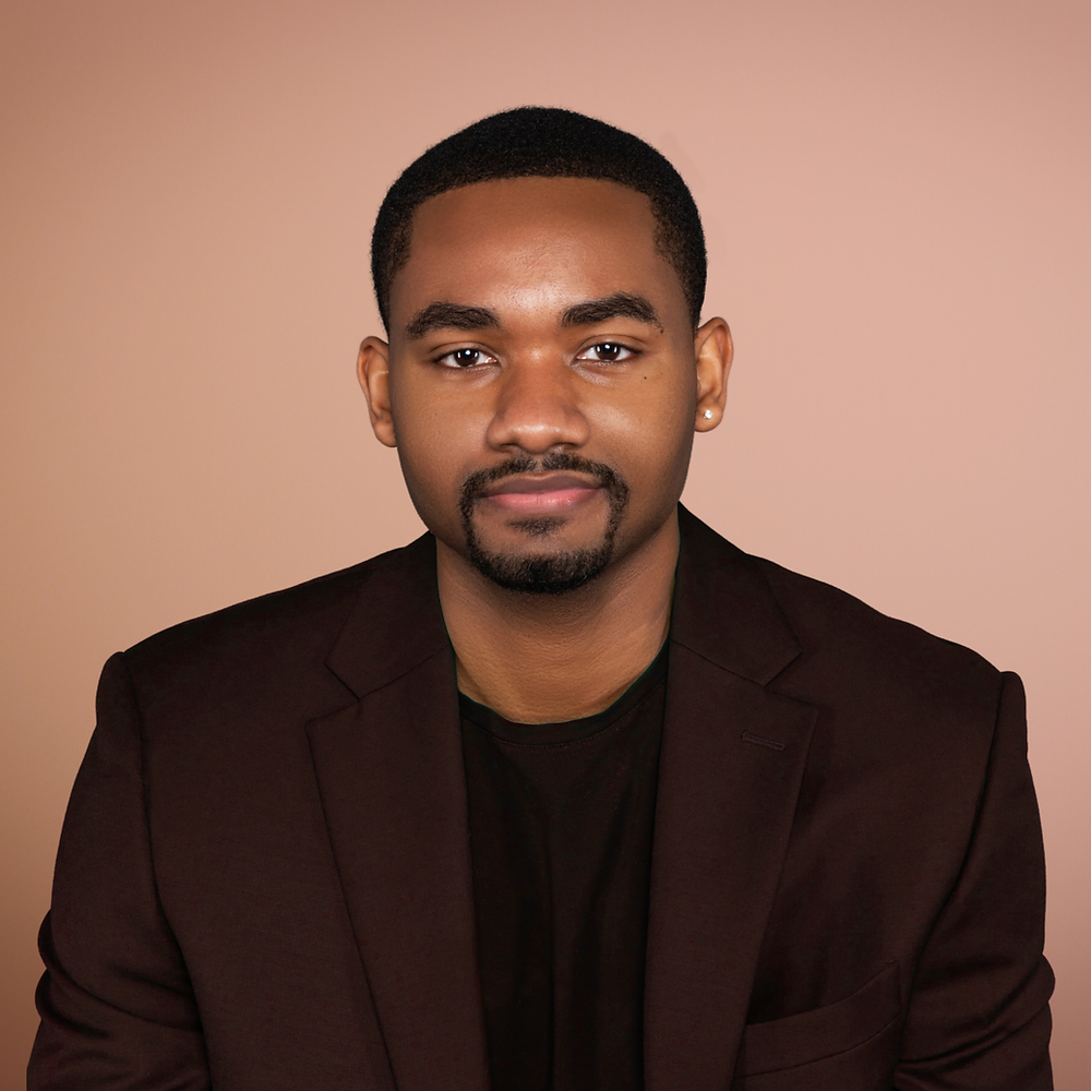 Artist Jonte Drew, young black man with goatee wearing dark maroon suit looks confidently at the camera