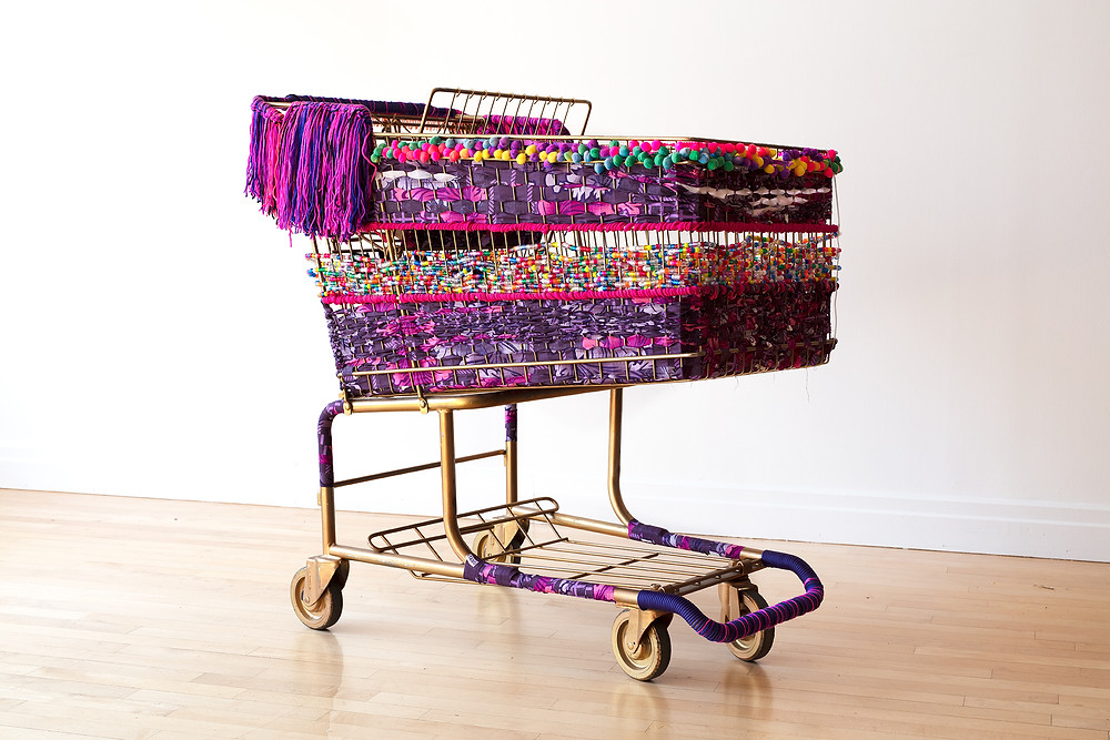 """1"""" cut strips of African print fabric, acrylic yarn, pony beads, pom poms, bells, 850 paracord, cool LED lights on a gold recovered shopping cart."""