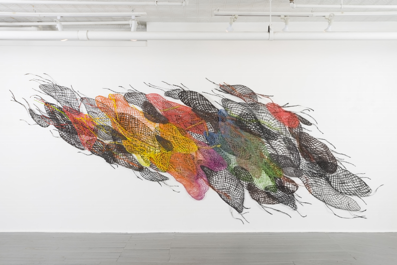 Image of colorful handmade paper nets compiled in huge installation across a white gallery wall resembling a swarm