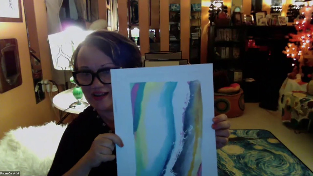 Artist Karen Carattini, an older woman with short black hair and thick black eye glasses, holds up a piece of her watercolor artwork on Zoom.