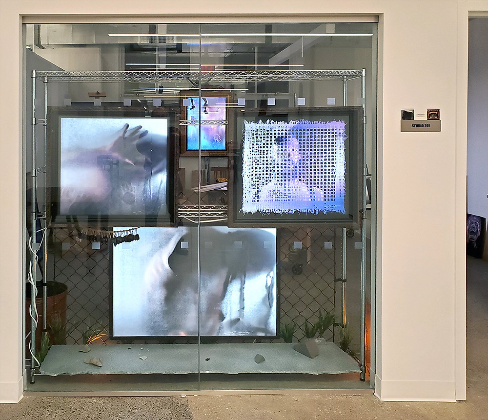 Entrance of Studio 201 at 150 Bay Street, glowing monitors and screens with multicolor images.