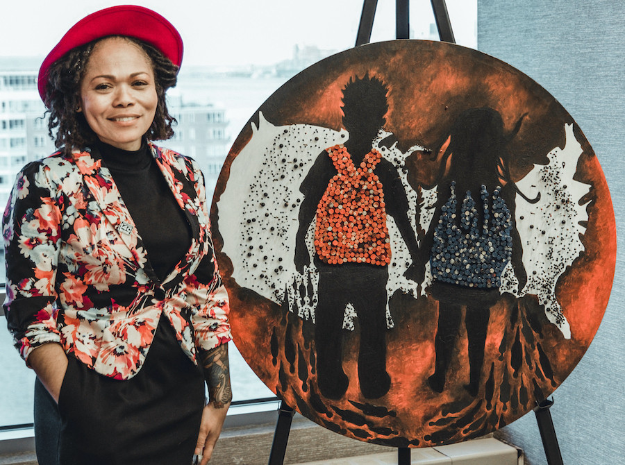 "Artist Danielle Scott stands next to her 36 inch diameter circular mixed media work entitled ""They carry the truth in their backpacks."" The artwork is made with paint and bullet casings and depicts her son and daughter with bullet-filled backpacks silhouetted against a map of the US."