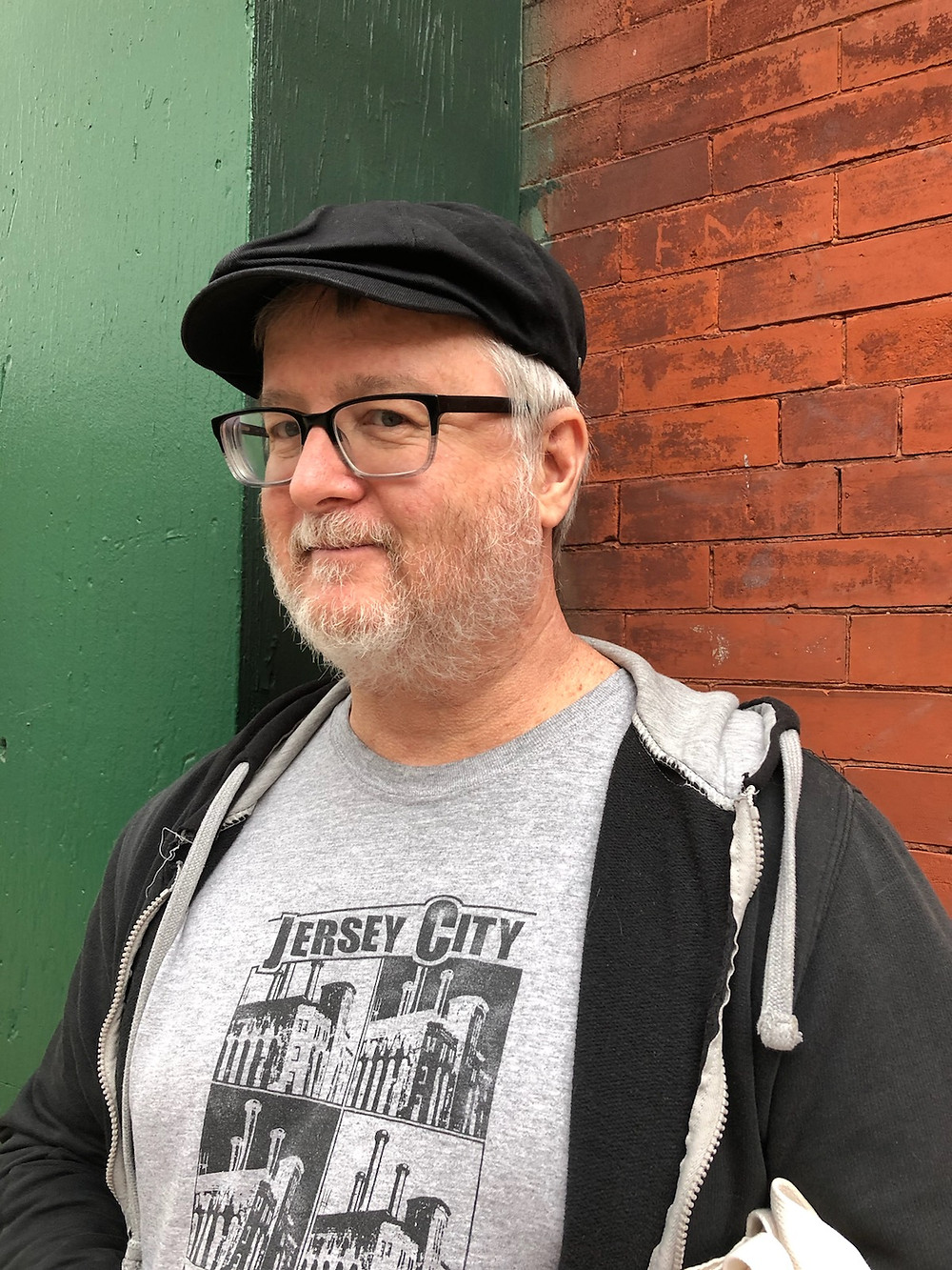 Jack is shown standing against a wall, part red brick & part wood painted 2 shades of green. He has a grey beard & hair. Is wearing black chunky glasses, black cap, a black unzipped hoodie, and a grey Jersey City t-shirt with 4 images of The Powerhouse Building.