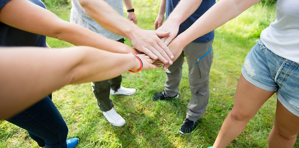 Volunteers putting their hands on top of each other in a circle formation