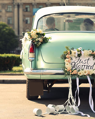 Wedding couple in car decorated with pla