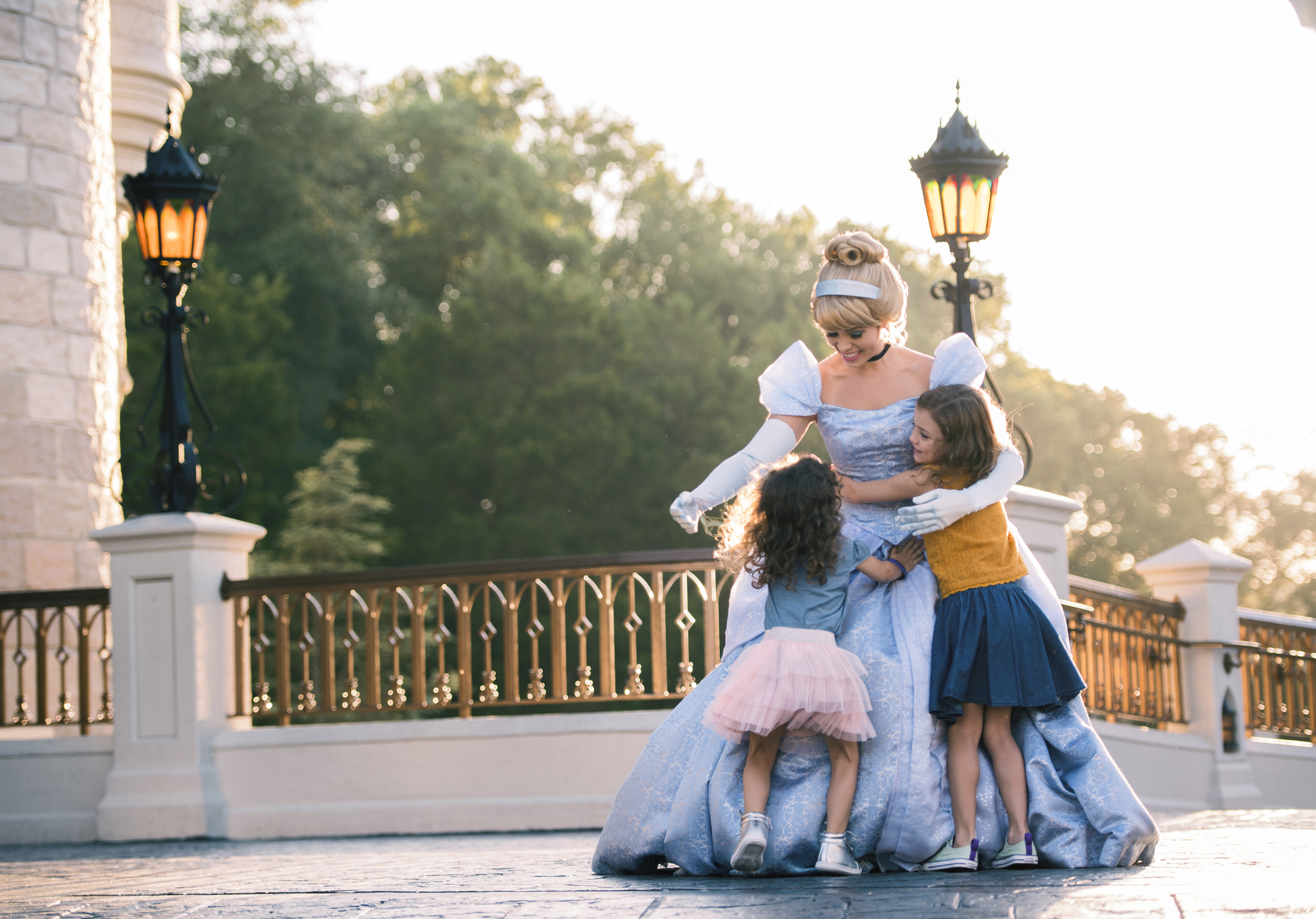 Two little girls hug Cinderella in front of her castle at Magic Kingdom
