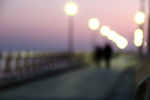 Blurry image of a couple on a bridge walking.
