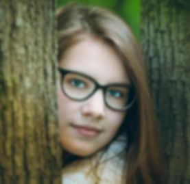 A pre-teen child wearing eye glasses peeing through two tree branches