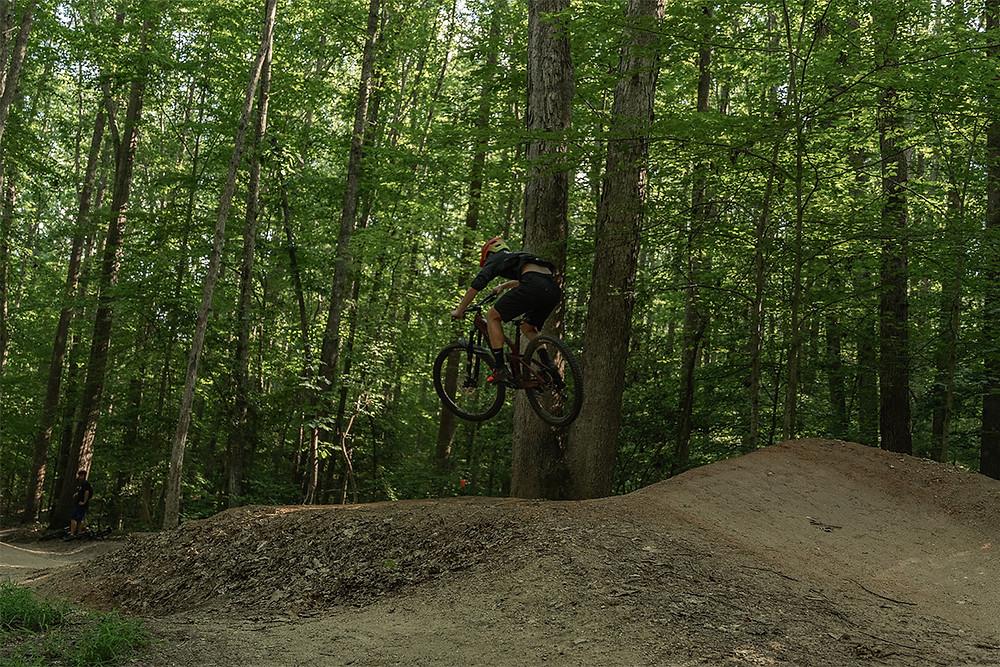 Mountain biker jumping off a dirt bump in forest