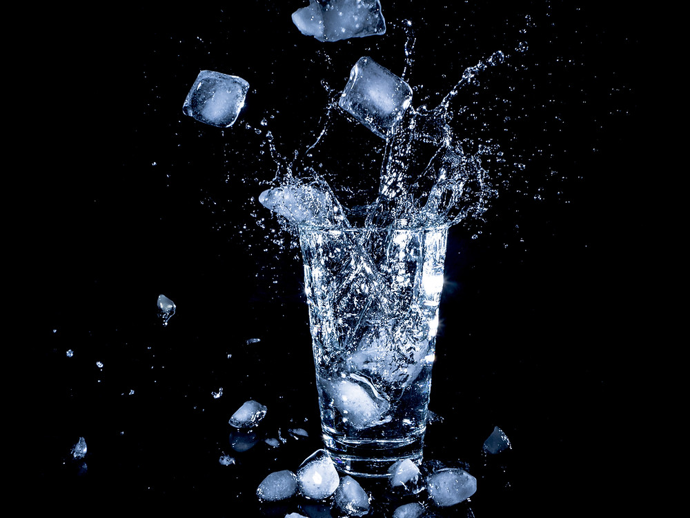 ice cubes falling into glass of water
