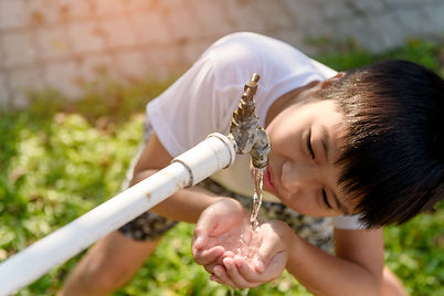 Young person drinking water in the garden