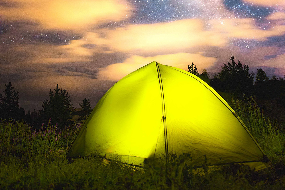 Glowing green tent under the stars