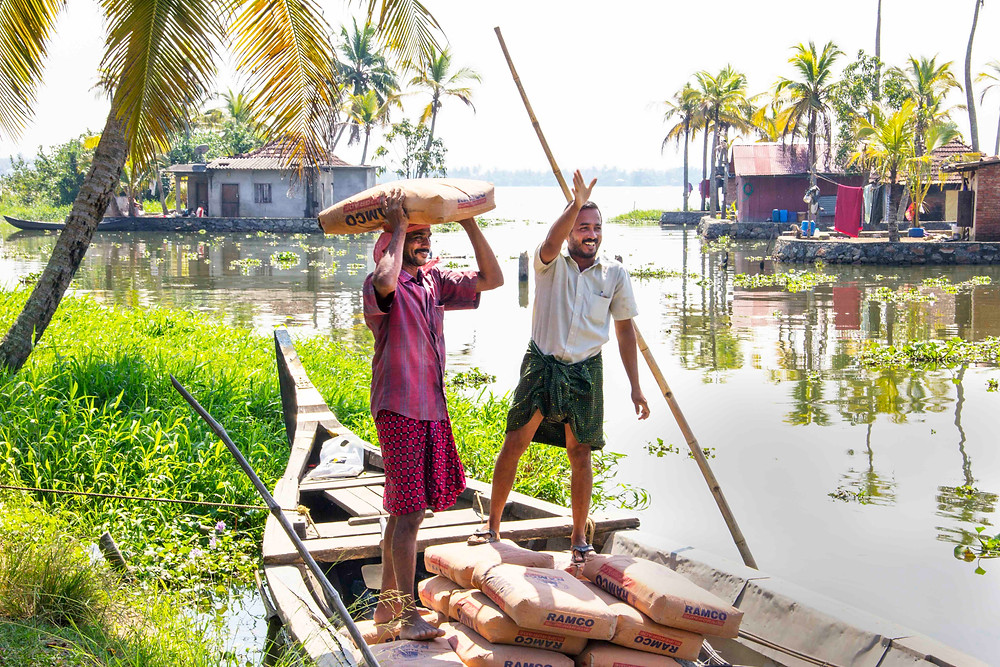 Men with house building supplies on canoe, Kerala India