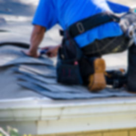 repairing the roof of a home; A worker r