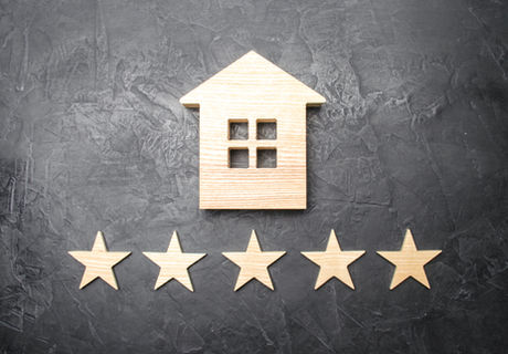 Wooden house and five stars on a gray ba