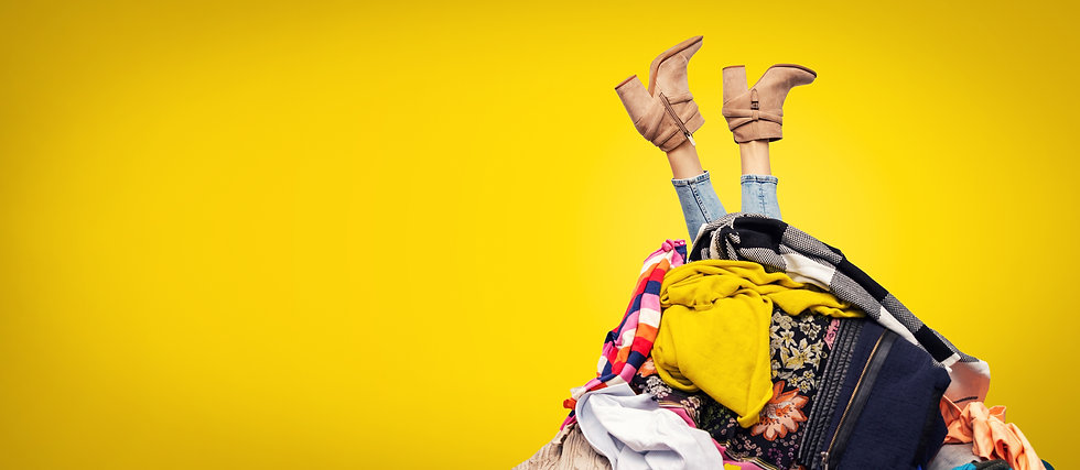 woman legs out of clothes pile on yellow