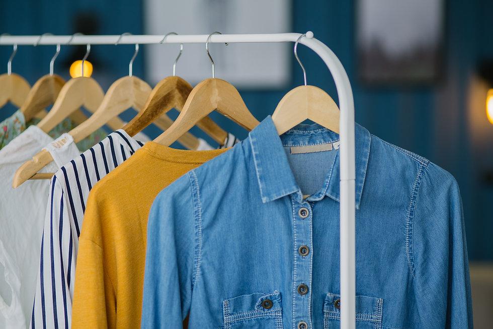 Clothes hang on wooden coat hangers in c