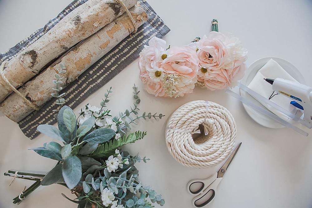 Wooden rod, silk flowers, craft cord, scissors, and hot glue gun