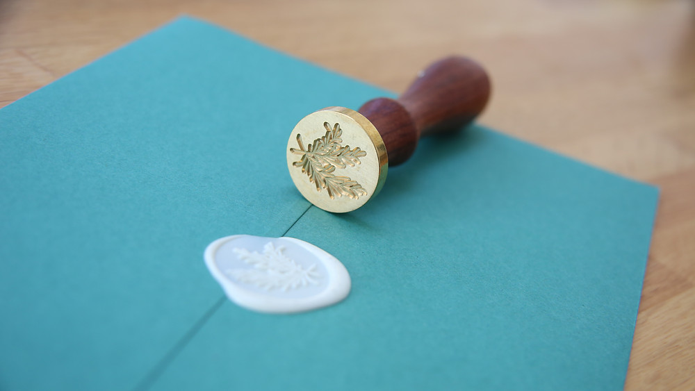 White wax seal and wax stamp with rosemary leaves