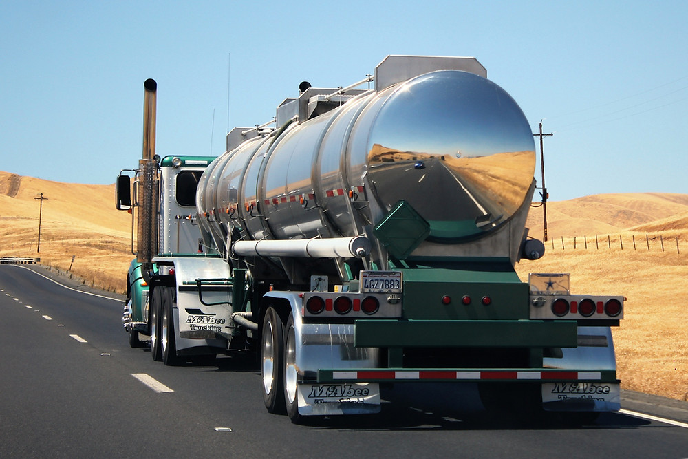 fuel tanker traveling down two lane country highway