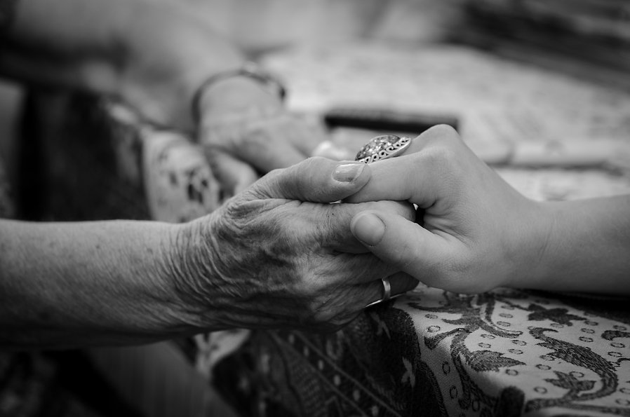 A young hand holding an elderly pair of
