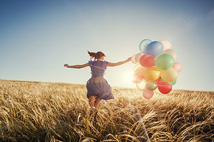 Girl running on the field with balloons
