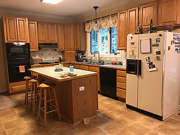 Outdate kitchen with island and refridgerator.