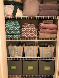 Organized linen closet wth labeled bins by Solutions for Stuff
